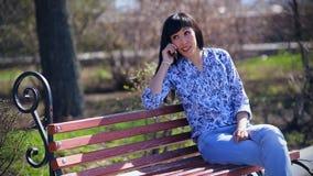 Mooie Aziatische meisjeszitting in een park op een bank in jeans en het spreken op de telefoon stock footage