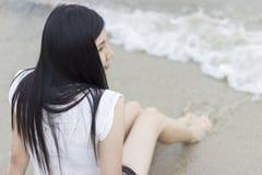 Mooie Aziatische modelzitting bij het strand Stock Afbeelding