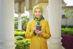 Mooie Aziatische moslimvrouw die mobiele telefoon met behulp van stock fotografie