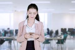 Mooie Aziatische onderneemster die tekstbericht verzenden op kantoor stock foto