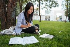 Mooie Aziatische student die verslagen in document notitieboekje bijhouden terwijl Stock Afbeelding