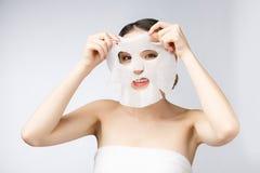 Mooie Aziatische vrouw die document bladmasker op haar toepassen gezichts witte achtergrond royalty-vrije stock foto