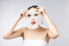 Mooie Aziatische vrouw die document bladmasker op haar toepassen gezichts witte achtergrond stock foto