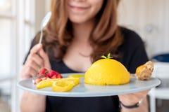 Mooie Aziatische vrouw die een plaat van oranje cake met gemengd fruit en een lepel in koffie houden royalty-vrije stock fotografie