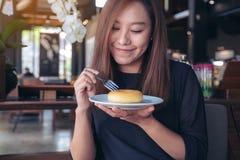 Mooie Aziatische vrouw die een vork houden om een stuk van doughnut met gevoel te snijden gelukkig in koffie stock foto's