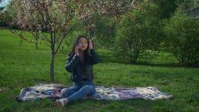 Mooie Aziatische vrouw die op telefoon in de lentepark spreken stock videobeelden