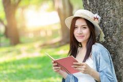 Mooie Aziatische vrouw die roze boek in het park lezen royalty-vrije stock foto's