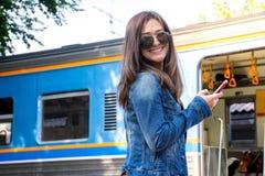 Mooie Aziatische vrouw die zonnebril dragen die camera bekijken die smartphone met treinachtergrond gebruiken stock afbeelding