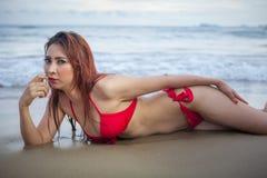 Mooie Aziatische vrouw in het rode bikini stellen stock fotografie