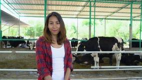 Mooie Aziatische vrouw of landbouwer met en koeien in koeiestal bij zuivel landbouwbedrijf-bewerkt, en veeteeltconcept stock videobeelden