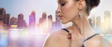 Mooie Aziatische vrouw met oorringsnacht over stad Stock Foto