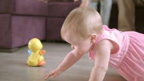 Mooie baby die op vloer thuis kruipen Gelukkig familieconcept stock videobeelden