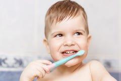 Mooie baby die zijn tanden met een tandenborstel in de badkamers borstelen royalty-vrije stock foto