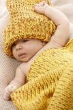 Mooie baby in geel breigoed Stock Fotografie