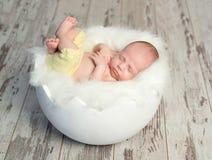 Mooie baby in gele broek op witte wieg zoals shell Stock Foto