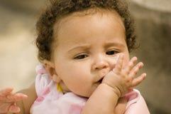 Mooie baby met hand bij mond Stock Afbeelding