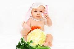 Mooie baby met wortelen Stock Afbeeldingen