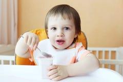 Mooie baby met youghourt Stock Afbeeldingen