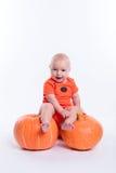 Mooie baby in oranje t-shirt op een witte zitting als achtergrond o stock foto's