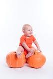 Mooie baby in oranje t-shirt op een witte zitting als achtergrond o royalty-vrije stock afbeeldingen