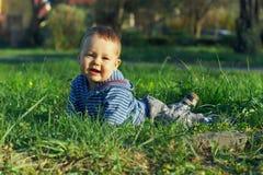 Mooie babyjongen die op groen gras ligt Royalty-vrije Stock Fotografie