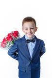 Mooie babyjongen in een kostuum met een boeket van rode rozen op een witte achtergrond Stock Foto