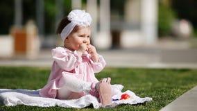 Mooie bakken de baby-meisje plaatsing op het groene gras en het eten in het park stock videobeelden