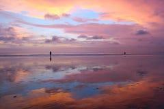 Mooie Balinese zonsondergang bij Kuta-strand met volkeren en hemelbezinning in zand Royalty-vrije Stock Fotografie