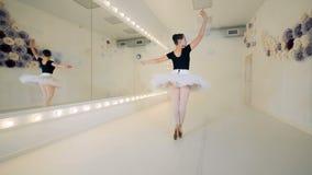 Mooie balletstudio met een damedanser die het spinnen bewegingen uitvoeren stock video
