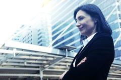 Mooie bedrijfs en vrouw die de bureausbouw achtergrond glimlachen kijken stock foto