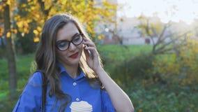 Mooie bedrijfsdame die op telefoon, het drinken koffie spreken en het glimlachen bij park 4K stock footage