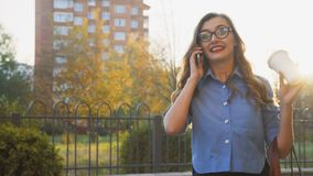 Mooie bedrijfsdame met koffie het in hand spreken op telefoon en het glimlachen 4K stock footage