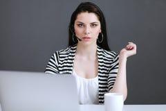 Mooie bedrijfsvrouw die bij haar bureau met hoofdtelefoon en laptop werken Stock Fotografie
