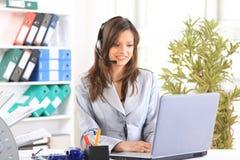 Mooie bedrijfsvrouw die bij haar bureau werkt met stock foto's