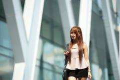 Mooie bedrijfsvrouw die buiten haar bureau met aktentas lopen Stock Afbeelding