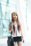 Mooie bedrijfsvrouw die buiten haar bureau met briefca lopen Royalty-vrije Stock Foto