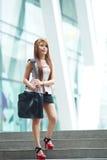 Mooie bedrijfsvrouw die buiten haar bureau met briefca lopen Stock Afbeeldingen