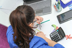 Mooie Bedrijfsvrouw die investeringsgrafieken met calculato analyseren stock afbeeldingen