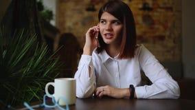 Mooie bedrijfsvrouw die op de telefoon spreken die en over haar reis op vakantie glimlachen spreken Close-up stock footage