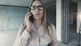 Mooie bedrijfsvrouw die op een smartphone spreken, die door onvolledige ruimten van de nieuwe bouw gaan stock videobeelden