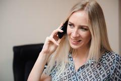 Mooie bedrijfsvrouw die op mobiele telefoon spreekt Het jonge vrouwelijke modelwerk met verkoop in bureau stock afbeelding