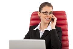 Mooie bedrijfsvrouw die op mobiele telefoonzitting spreken op een rode stoel in bureau Stock Afbeeldingen