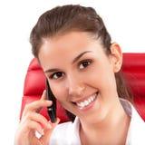 Mooie bedrijfsvrouw die op mobiele telefoonzitting spreken op een rode stoel in bureau Royalty-vrije Stock Foto