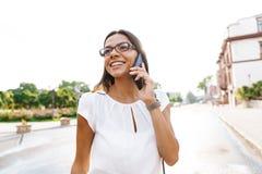 Mooie bedrijfsvrouw die in openlucht het spreken lopen door mobiele telefoon royalty-vrije stock afbeelding