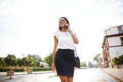 Mooie bedrijfsvrouw die in openlucht het spreken lopen door mobiele telefoon stock afbeeldingen
