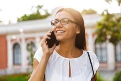 Mooie bedrijfsvrouw die in openlucht het spreken lopen door mobiele telefoon royalty-vrije stock foto