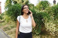 Mooie bedrijfsvrouw die in openlucht het spreken lopen door mobiele telefoon stock foto