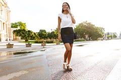 Mooie bedrijfsvrouw die in openlucht het spreken lopen door mobiele telefoon royalty-vrije stock foto's