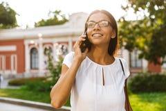 Mooie bedrijfsvrouw die in openlucht het spreken lopen door mobiele telefoon stock foto's