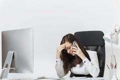 Mooie bedrijfsvrouw in kostuum en glazen die bij computer met documenten in licht bureau werken stock foto